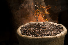 Coffee beans falling to the sack full of smoky coffee beans. Royalty Free Stock Photography