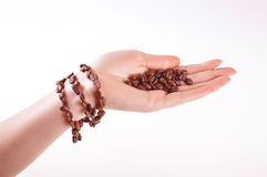 Coffee beans on a female hand with bracelet Royalty Free Stock Photography