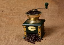 Coffee Beans filled in retro grinder Machine on jute fabric.  Royalty Free Stock Images