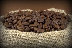 Coffee beans in a flax sack on brown background Royalty Free Stock Photo