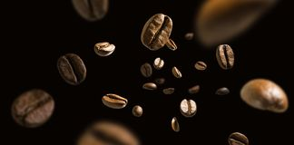 Coffee beans in flight on a dark background royalty free stock image