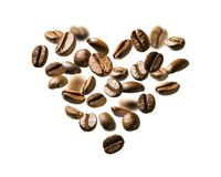 Coffee beans in flight in the shape of a heart.  royalty free stock photos