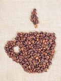 Coffee beans in the form of cup. On background of burlap Royalty Free Stock Photo