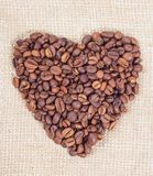 Coffee beans in the form of heart. On background of burlap Stock Photo