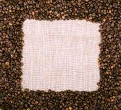 Coffee beans frame over burlap textile Royalty Free Stock Photos