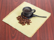 Coffee beans and freshly brewed coffee in black ceramic cup Royalty Free Stock Photography