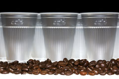 Coffee beans in front of plastic cups Stock Images