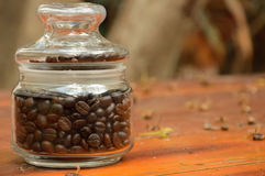 Coffee beans in glass bottle. On wood Royalty Free Stock Image