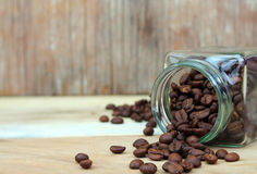 Coffee beans in glass bottle. On wood Royalty Free Stock Photo