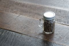 Coffee beans in glass bottles with old wood floor Stock Image