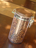 Coffee beans in glass container on wooden table. Royalty Free Stock Photography