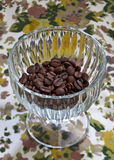 Coffee beans in a glass dish on a floral backgroun Royalty Free Stock Photos