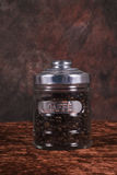 Coffee beans in glass jar. Closeup of dark roasted coffee beans in glass jar with brown background Royalty Free Stock Images