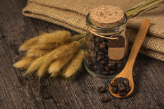 Coffee beans in a glass jar. On the background of burlap and wheat spikelets Royalty Free Stock Images