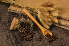 Coffee beans in a glass jar. On the background of burlap and wheat spikelets Stock Photography