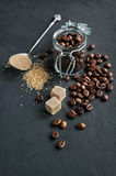 Coffee beans in a glass jar and brown cane sugar Stock Image
