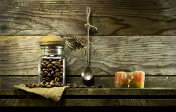 Coffee beans in a glass jar and spoon on shelf. Royalty Free Stock Image