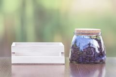Coffee beans in a glass jar with a wooden crate on a wooden tabl. E Royalty Free Stock Photos