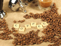 Coffee beans, glass mug, tamper in front of a group handle with the letters coffee on a hessian background Stock Photo