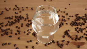 Coffee beans and a glass of water stock footage