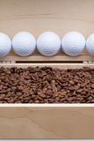 Coffee beans and golf balls in an open box Royalty Free Stock Photo