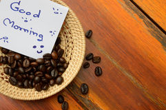 Coffee beans and good morning note in basket. On the wooden background Stock Photo