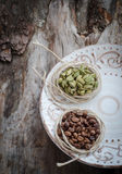 Coffee beans and green cardamom on aged wood Stock Photography
