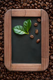 Coffee beans with green leaves on the chalkboard menu Stock Image