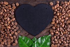 Coffee beans and green leaves with heart on an old wooden desk. Love to coffee background. Love and coffee. Stock Photography