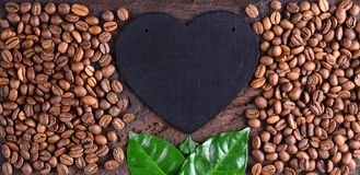 Coffee beans and green leaves with heart on an old wooden desk. Top view of coffee beans with a copy space for your text. Royalty Free Stock Photography
