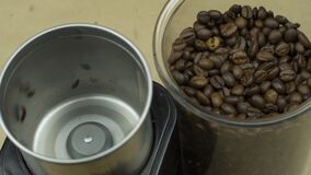 Coffee beans grind in electric mill, beige background. Energy morning concept