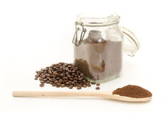 Coffee beans and grinded on white. Grinded coffee on a wood spoon with a pile of beans and a jar on the background Royalty Free Stock Photo