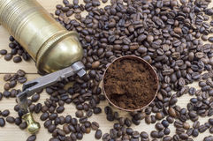 Coffee beans, grinder and on a wooden table with grounded coffe Royalty Free Stock Photos