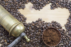 Coffee beans, grinder and on a wooden table with grounded coffe Royalty Free Stock Image