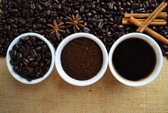 Coffee beans, ground coffee, and black coffee in white cups. With coffee beans in background on burlap Stock Images