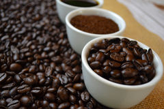 Coffee beans, ground coffee, and black coffee in white cups. With coffee beans in background on burlap Royalty Free Stock Photography