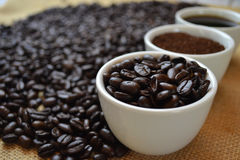 Coffee beans, ground coffee, and black coffee in white cups. With coffee beans in background on burlap Royalty Free Stock Photo