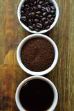Coffee beans, ground coffee, and black coffee in white cups. On wood table Royalty Free Stock Photo
