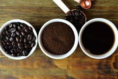 Coffee beans, ground coffee, and black coffee in white cups. On wood table Stock Photo
