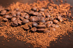 Coffee beans and ground coffee oт brown table. Coffee beans and ground coffee on dark brown table Royalty Free Stock Image