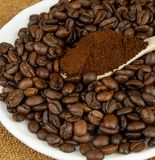 Coffee beans and ground coffee in a spoon. Royalty Free Stock Image