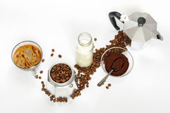 Coffee beans and ground, milk in a bottle, Moka pot. Coffee with milk in a glass cup, coffee beans, ground coffee and Moka coffee pot on white background stock photos
