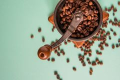 Coffee beans in a hand-held coffee grinder on a tender green bac Royalty Free Stock Images
