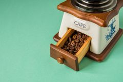 Coffee beans in a hand-held coffee grinder on a tender green bac Stock Image