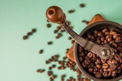 Coffee beans in a hand-held coffee grinder on a tender green bac Stock Photos