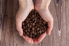 The coffee beans in a hands Royalty Free Stock Image