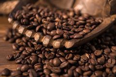 Coffee beans, hands. Coffee beans in wooden hands on table, brown, warm colors Royalty Free Stock Photography