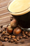 Coffee beans and hazelnuts near espresso in a shor Stock Image
