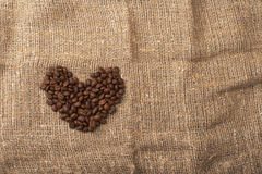 Coffee beans heart. On a piece of coarse cloth Royalty Free Stock Images