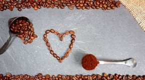 Coffee beans heart from Fair Trade beans with spoon at grey kitchen worktop background royalty free stock photo